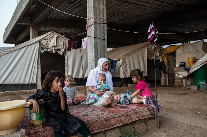 An elderly Yazidi woman tends to young children beside a half-constructed building in an internally displaced persons (IDP) camp ... [LCID: ref01]