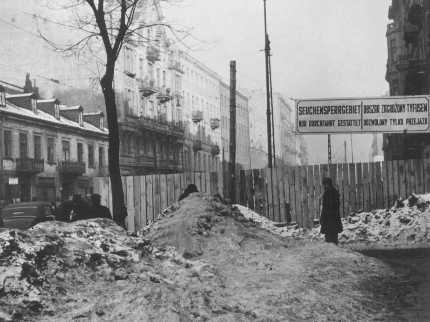"""<p>مدخل الحي اليهودي بوارصوفيا. وتشير العالمة: """"منطقة محاصرة بسبب وجود وباء: يسمح الدخول إلا داخل وسيلة نقل."""" وارصوفيا, بولندا. فبراير 1941.</p>"""
