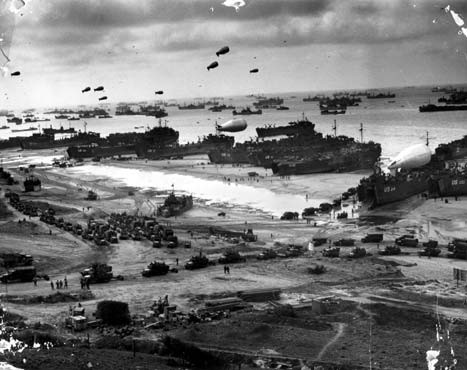 The Normandy beach as it appeared after D-Day. Landing craft on the beach unload troops and supplies transferred from transports offshore.