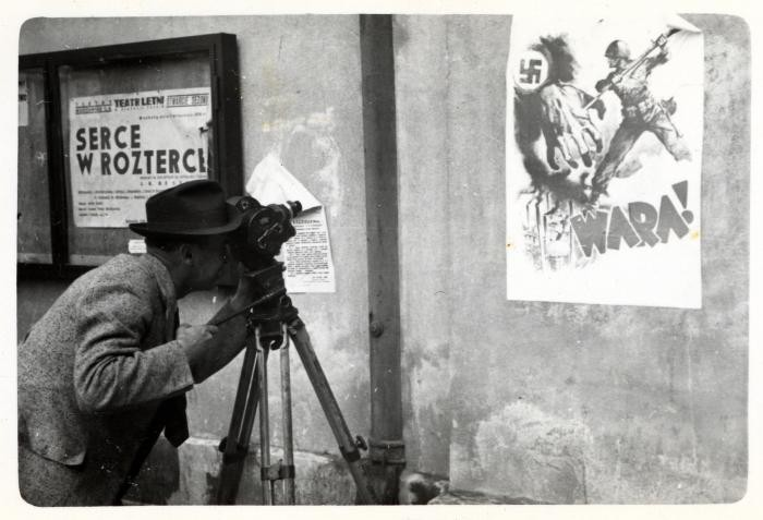 Julien Bryan films an anti-Nazi propaganda poster in Warsaw