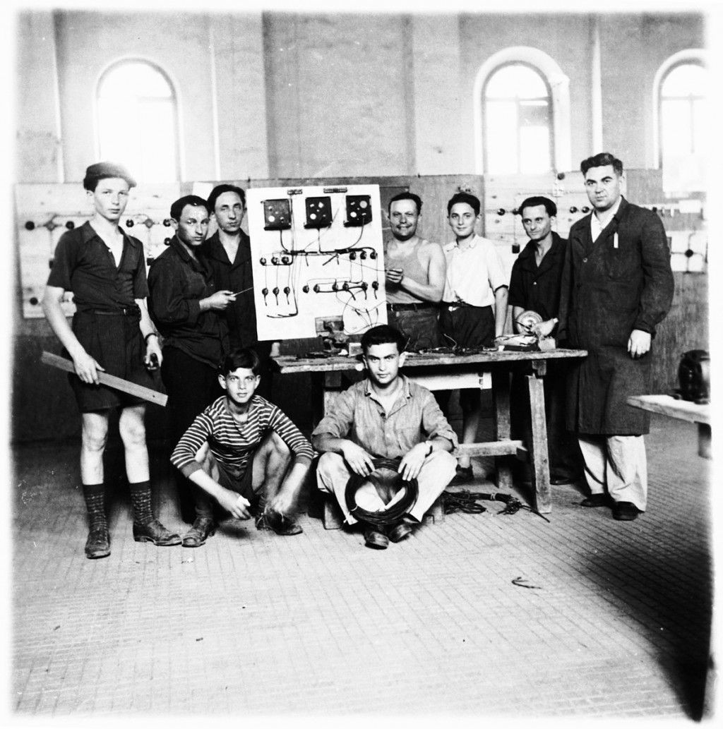 """<p>Jewish teenagers study electricity at a vocational ORT (Organization for Rehabilitation through Training) school in the <a href=""""/narrative/53735"""">Cremona</a> displaced persons (DP) camp, Italy, 1945–1947. Shie Zoltak is standing on the far left. Standing on the far right is Shie's uncle, Abraham Lisogurski, who is the instructor.</p>"""