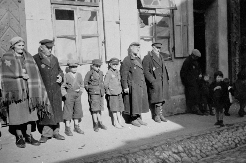 German Jewish adults and children wearing compulsory Jewish badges are lined up against a building. [LCID: 11191]