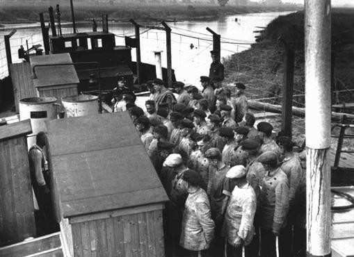 <p>Many of the early concentration camps were improvised. Here, roll call is held for political prisoners aboard a ship used as a floating concentration camp. Ochstumsand camp, near Bremen, Germany, 1933 or 1934.</p>