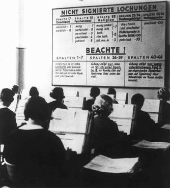 "<p><a href=""/narrative/4164/en"">German women</a> at work in the offices of the German Census Bureau. The board gives directions for tabulation: the center column instructs that number 3 is the indicator to be used for Jews. Germany, 1933.</p>"