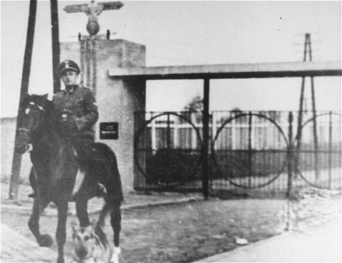 <p>SS Second Lieutenant Gustav Willhaus, camp commandant, rides past the main gate of the Janowska concentration camp. The road from the street and into the camp was paved with tombstones the Nazis removed from Jewish cemeteries. Janowska, Poland, between September 1942 and November 1943.</p>