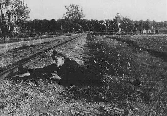 <p>Jewish partisan Boris Yochai plants dynamite on a railroad track. Vilna, 1943 or 1944.</p>