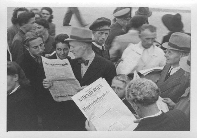 """<p>İnsanlar Uluslararası Askerî Mahkeme tarafından verilen hükümleri bildiren """"Nurnberger"""" gazetesinin özel baskısını almak için sokakta toplanıyor. 1 Ekim 1946.</p>"""