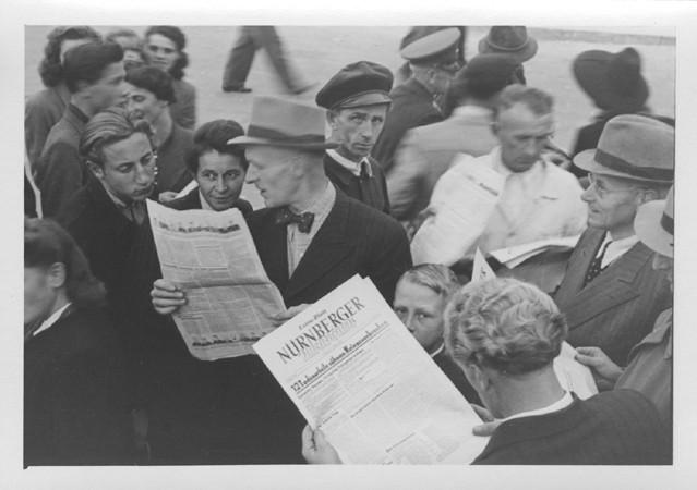 "<p>人们聚集在街道上,读报纸上的""纽伦堡""特刊,上面报道了国际军事法庭的宣判结果。拍摄时间:1946 年 10 月 1 日。</p>"