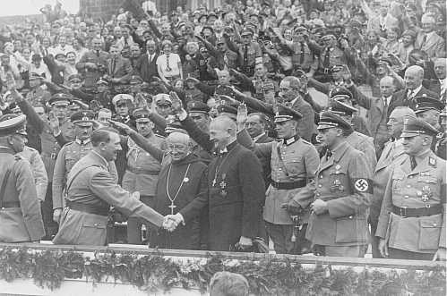 "<p><a href=""/narrative/43"">Adolf Hitler</a> greets Reich Bishop Ludwig Mueller at a Nazi Party Congress. Roman Catholic Abbot Alban Schachleiter stands between Hitler and Mueller. Nuremberg, Germany, September 1934.</p>"