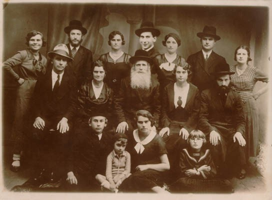 <p>In this 1934 portrait of Norman Salsitz's family, Norman is seated in the front row (at left). In the top row, center, an image of one of Norman's brothers has been pasted into the photograph. This is seen by comparing the size of the brother's face with the others pictured. Pasting in images of family members who could not be present during family portraits was common practice and in some cases the resulting composite images are the only remaining visual records of family groups.</p>