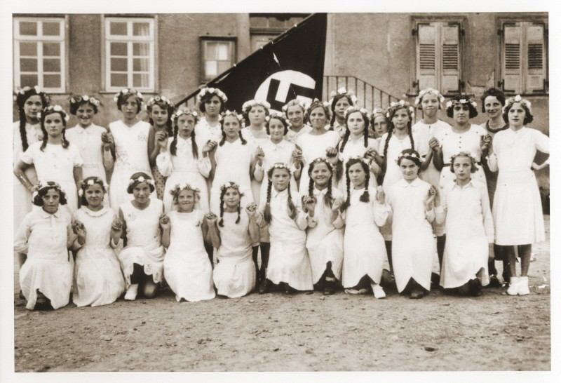 <p>Group portrait of German girls posing outside their school in front of a Nazi flag. Among those pictured is Lilli Eckstein six months before she was expelled from the school for being Jewish. Heldenbergen, Germany, 1935.</p>