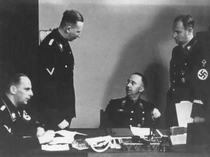 Heinrich Himmler (seated, center), chief of the SS, with Reinhard Heydrich (standing, left), chief of the Reich Main Security Office ... [LCID: 79625]