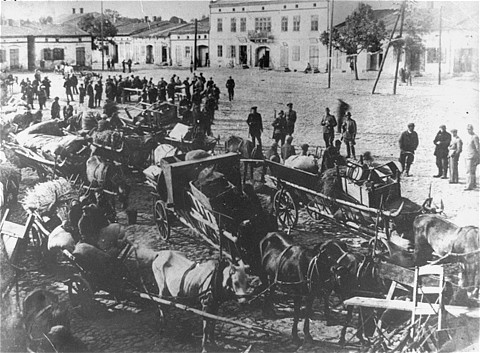 <p>German troops stand in the town sqaure of Przyrow where dozens of horse-drawn wagons are gathered presumably during a resettlement action. Przyrow, Poland,  ca. 1939-1943.</p>