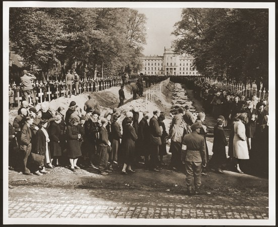 "<p>German civilians from Ludwigslust file past the corpses and graves of 200 prisoners from the nearby concentration camp of <a href=""/narrative/7988"">Wöbbelin</a>. The US Army ordered the townspeople to bury the corpses on the palace grounds of the Archduke of Mecklenburg. Germany, May 7, 1945.</p>