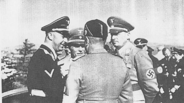 <p>Durante una visita a Alemania, el dictador italiano Benito Mussolini (de espaldas a la cámara) conversa con (de izquierda a derecha): el jefe de las SS, Heinrich Himmler; el ministro de propaganda nazi, Joseph Goebbels; y el gobernador nazi de Polonia, Hans Frank. Alemania, 1941.</p>
