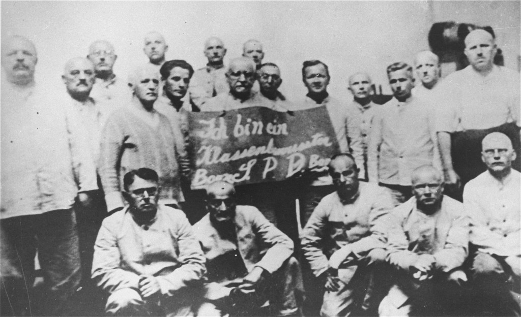 "<p>Humiliation of political prisoners: Social Democratic Party (SPD) inmates hold a placard which reads ""I am a class-conscious person, party boss/SPD/party boss."" <a href=""/narrative/4391"">Dachau</a> concentration camp, Germany, between 1933 and 1936.</p>"