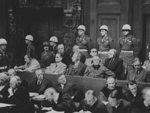 <p>ニュルンベルグの戦争犯罪人の国際軍事裁判で文書の提出を始める検察側に耳を傾ける被告たち。1945年11月22日。</p>