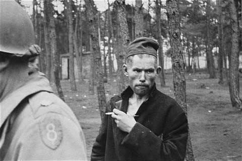 A survivor in Wöbbelin. The soldier in the foreground of the photograph wears the insignia of the 8th Infantry Division. [LCID: 09287]