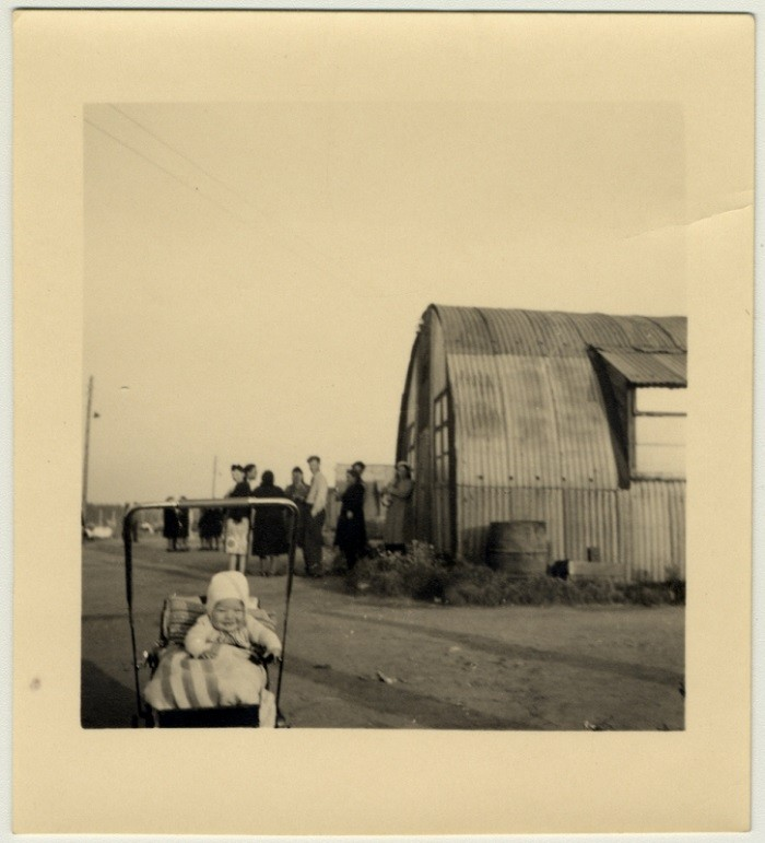 A young baby sits in its carriage next to a Quonset hut in Babenhausen displaced persons camp. [LCID: 54644]