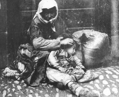 An Armenian woman and her child sit on a sidewalk next to a bundle of their possessions. [LCID: 34283]