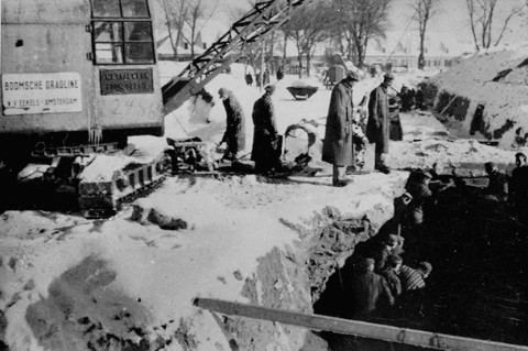 Prisoners at forced labor digging a drainage or sewage trench in Auschwitz. [LCID: 85023]