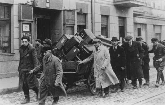 "<p>Jews deported from Prague, <a href=""/narrative/7295"">Czechoslovakia</a>, move their belongings through the streets of the <a href=""/narrative/2152"">Lodz</a> ghetto in occupied Poland. November 20, 1941.</p>"