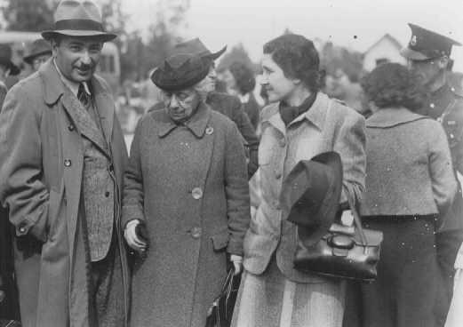 """<p>Eliahu Dobkin of the Jewish Agency (left) and Henrietta Szold, founder of the Hadassah Women's Zionist Organization (second from left), await the arrival of the """"<a href=""""/narrative/11006/en"""">Tehran Children</a>."""" Atlit, Palestine, February 18, 1943.</p>"""