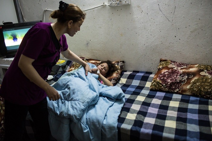 A mother checks on her sick daughter inside the container where they live in an internally displaced persons (IDP) camp near Erbil, ... [LCID: ref03]