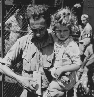 "<p>Jewish refugees from Europe arrive at the emergency refugee shelter at Fort Ontario, in the <a href=""/narrative/9681"">United States</a>. A father, holding his daughter, checks his tags. Oswego, New York, United States, August 4, 1944.</p>"
