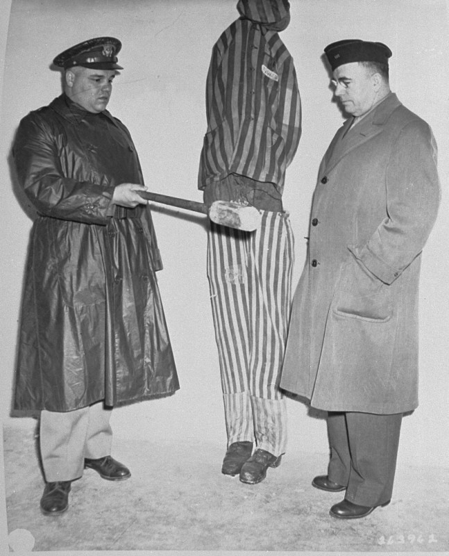 <p>During an inspection by US Army chaplains of the newly liberated Buchenwald concentration camp, G. Bromley Oxnam (right) views a demonstration of how prisoners were tortured in Buchenwald. Oxnam was the Methodist bishop of New York and President of the Federated Council of Churches of Christ in America. Buchenwald, Germany, April 27, 1945.</p>