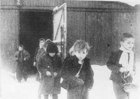 Soon after liberation, surviving children of the Auschwitz camp walk out of the children's barracks. [LCID: 70262]