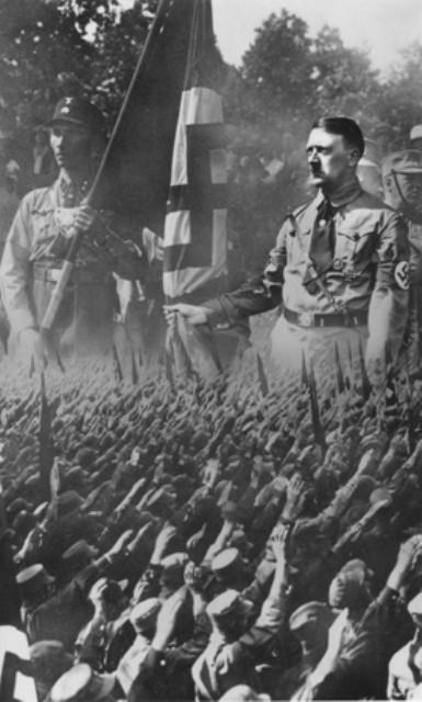 <p>Montagem de um cartão postal mostrando uma multidão de alemães em pose de saudação sobrepostos a uma imagem ampliada de Hitler e de um soldado da tropa de choque nazista. Munique, Alemanha.  Foto tirada por volta de 1932.</p>