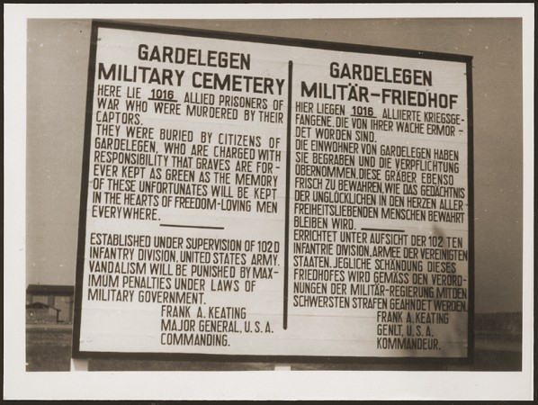 "<p>A sign at the military cemetery in <a href=""/narrative/8101"">Gardelegen</a> in memory of the prisoners who were killed by the SS in a barn near the town. Germany, April 18, 1945.</p>"
