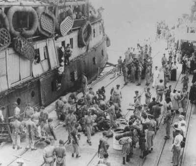 """As UN official Emil Sandstroem (bottom right, white hat) looks on, British soldiers remove Jewish refugees from the ship """"Exodus ... [LCID: 69913]"""
