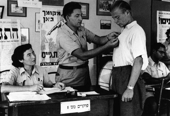 <p>In the British army recruitment office in Tel Aviv, an official pins the symbol of the volunteer Jewish Brigade onto the shirt of a new recruit. Tel Aviv, Palestine, 1940-1941.</p>