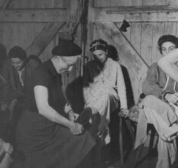 Soon after liberation, a British woman helps a camp survivor try on shoes. [LCID: 45014]