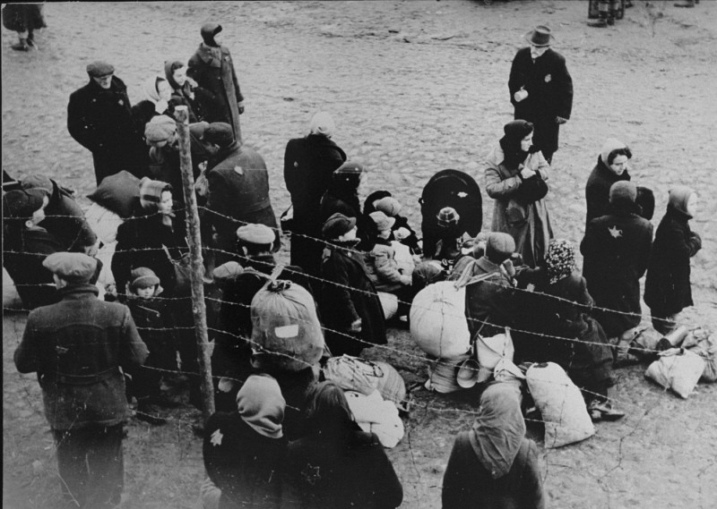 Jewish families with bundles of belongings during deportation from the Kovno ghetto to Riga in neighboring Latvia. [LCID: 81090]