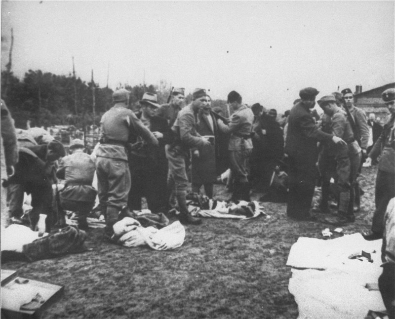 Ustasa (Croatian fascist) guards search prisoners and take their belongings upon arrival at Jasenovac concentration camp. [LCID: 68290c]