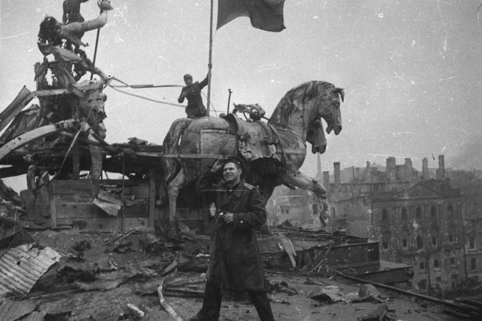 """<p><span style=""""font-weight: 400;"""">Soviet photographer Yevgeny Khaldei stands on top of the Brandenburg Gate in Berlin where he, along with a few Soviet soldiers, raised the Soviet flag. Berlin, Germany, May 1945.</span></p>"""