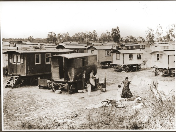 """<p>Romani (Gypsy) women boil laundry and hang it to dry in the middle of the camp at Marzahn. Germany, June 1936.</p> <p>Shortly before the opening of the 1936 Olympic Gamesin Berlin, the police ordered the arrest and forcible relocation of all <a href=""""/narrative/6716"""">Roma</a> in Greater Berlin to Marzahn, an open field located near a cemetery and sewage dump in eastern Berlin. Police surrounded all Romani encampments and transported the inhabitants and their wagons to Marzahn.</p>"""