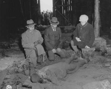 Three German mayors view the corpse of a prisoner burned alive in a barn by the SS while on a death march from Rottleberode, a subcamp ... [LCID: 45438]