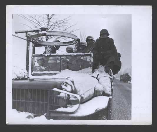 GIs move up to the front in open trucks in subzero weather to stop the German advance. [LCID: sc111]