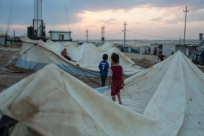Refugee boys from Syria play on old tents in the Domiz refugee camp outside Duhok, Iraqi Kurdistan. [LCID: ref09]