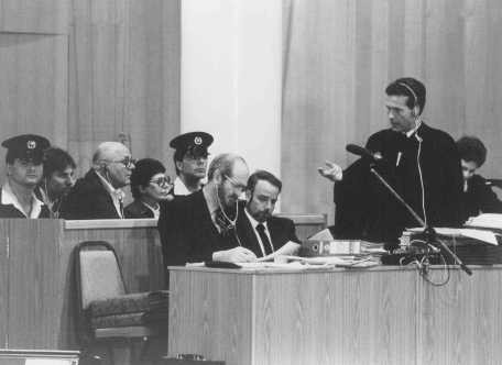 "<p>Chief defense attorney Mark O'Conner (standing) addresses a question to <a href=""/narrative/11530"">John Demjanjuk</a> during Demjanjuk's trial. Jerusalem, Israel, Feburary 16, 1987.</p>"