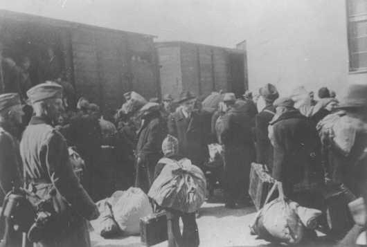 <p>Aleksander Belev, comisionado búlgaro para asuntos judíos (en el centro, con sombrero y de frente a la cámara), supervisa la deportación de los judíos. Skopje, Yugoslavia, marzo de 1943.</p>