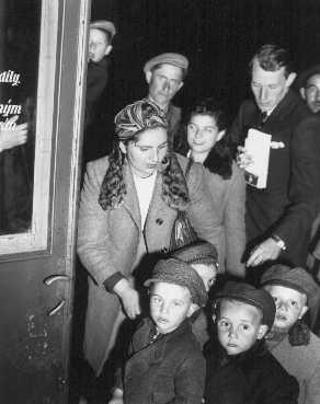 <p>Un assistant social de l'UNRRA (Administration des Nations Unies pour les secours et la reconstruction) aide des orphelins juifs polonais en route pour la France et la Belgique. Prague, Tchécoslovaquie, probablement en 1946.</p>