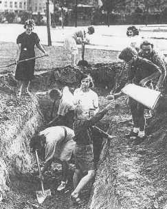 "<p>Men, women, and children dig defense ditches during the German siege of <a href=""/narrative/2014"">Warsaw</a>. Poland, September 1939.</p>"