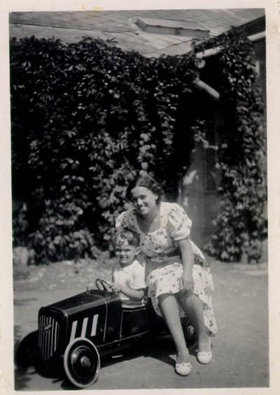 "<p>Photograph of a young <a href=""/narrative/10475"">Thomas Buergenthal</a> posing in his toy car as his mother sits alongside. 1936.</p>"