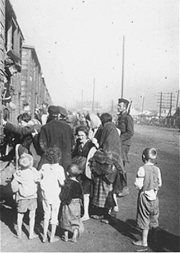 Under guard, Jewish men, women, and children board trains during deportation from Siedlce to the Treblinka killing center. [LCID: 11158]