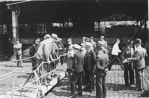 "<p>Belgian officials at the gangplank of the <a href=""/narrative/5063""><em>St. Louis</em></a> after the ship was forced to return to Europe from <a href=""/narrative/10734"">Cuba</a>. Belgium granted entry to some of the passengers. Antwerp, Belgium, June 1939.</p>"